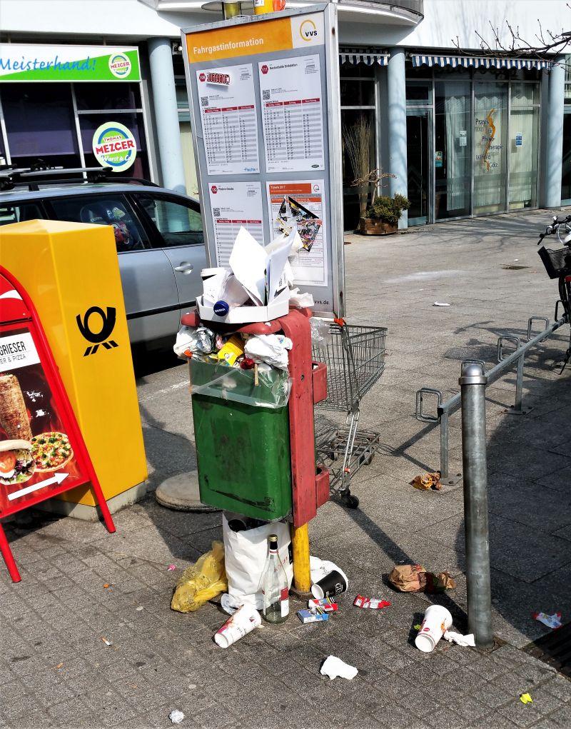 Ein grüner Müllbehälter ist überfüllt, die Reste liegen am Boden.