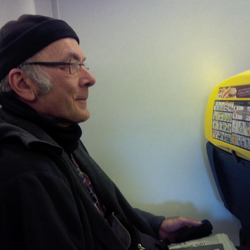 Der Autor Lothar Ulsamer mit Mütze an einem Fensterplatz ohne Fenster in einem Ryanair-Flieger.