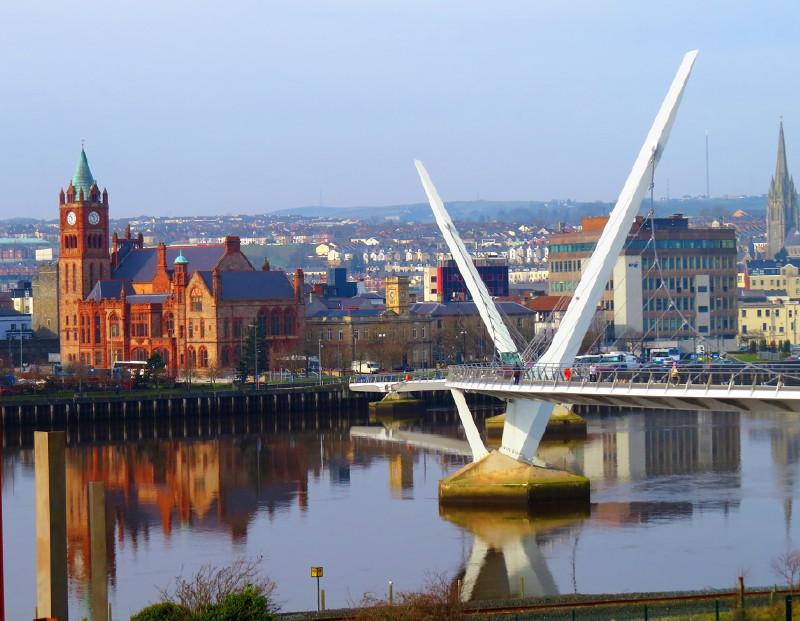 Eine moderne Brückenkonstruktion aus weißem Metall überspannt den Fluss.