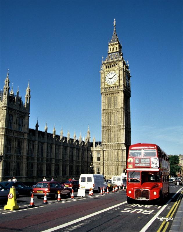 Der Big Ben in London, ein hoher Turm mit großer Uhr am Parlament. Im Vordergrund ein doppelstockiger roter Bus.
