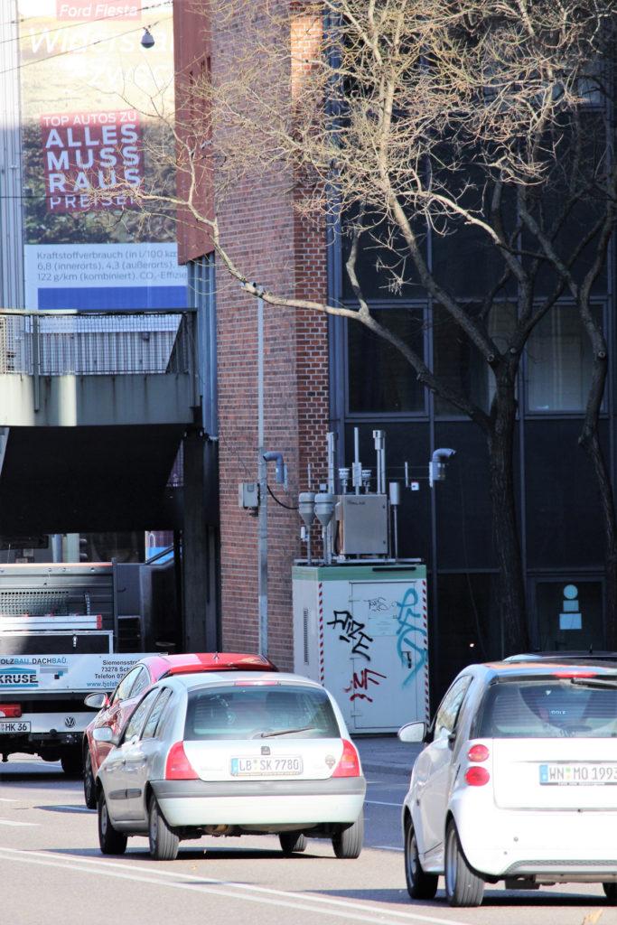 Fahrzeugkolonne, die sich an der Messstelle entlang bewegt. Hinter der Messtelle befindet sich eine Mauer und rechts das Gebäude.