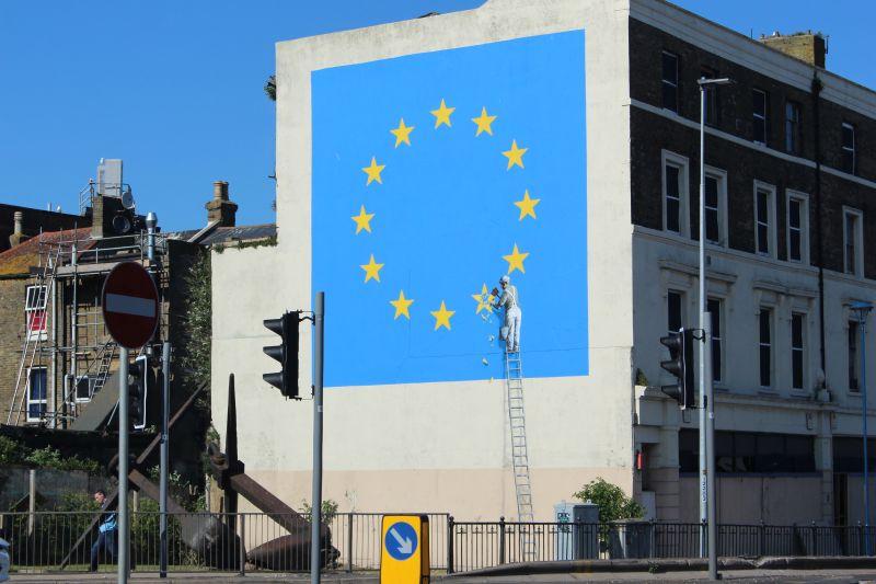 """Nachgebildete blaue EU-Flagge mit gelben Sternen an einer Hauswand in Dover. Eine """"Person"""" ist dabei, einen Stern zu entfernen."""
