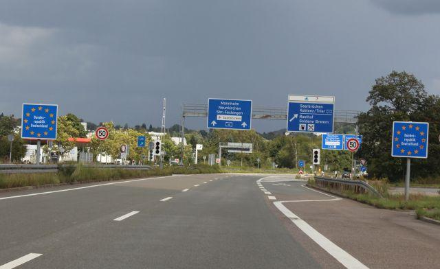 Das Bild zeigt die deutsch-französische Grenze ohne Kontrolle. Autobahnschilder im Hintergrund.