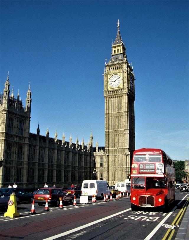 Blick auf den Big Ben in London. Im Vordergrund ein roter Doppeldeckerbus.