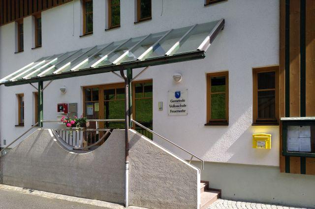 Schild an einem weißen Gebäude: Gemeinde, Volksschule, Feuerwehr.