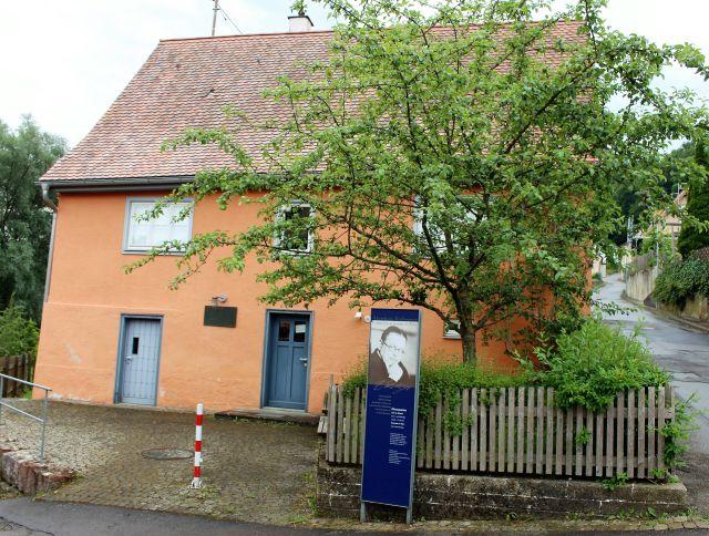 Blick auf das rötlih-orangene Geburtshaus von Matthias Erzberger. Im Vordergrund ein Baum und eine Stele mit einem Foto Erzbergers.