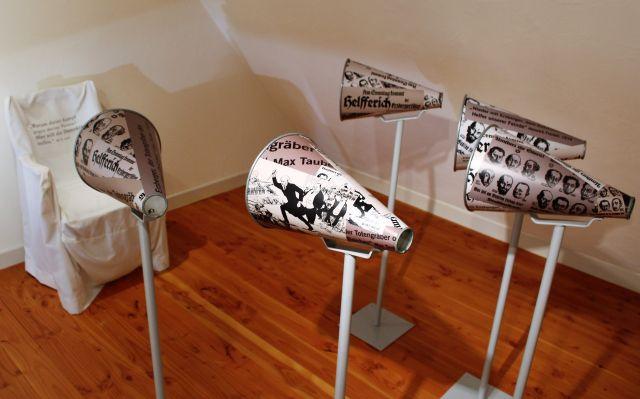 Zimmer im Geburtshaus und heutigen Museum. Trichter mit Zeitungsartikeln sind auf den Sessel gerichtet, in dem gewissermaßen Erzberger sitzt, der sich all die Verunglimpfungen anhören muss.