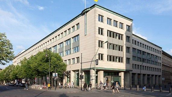 Helles Gebäude in Berlin, umgeben von einigen kleineren Bäumen.