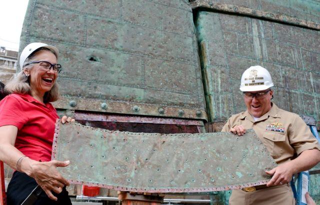 Eine Dame mit roten Bluse und ein Mann in Uniform, jeweils mit weißem Helm. Sie halten eine Kupferplatte in Händen, die am Schiff (im Hintergrund) besestigt wird.