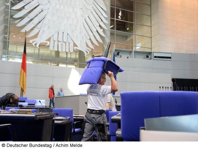 Ein Mann in T-Shirt und grauer Hose trägt einen blauen Sessel über dem Kopf durch den Plenarsaal.