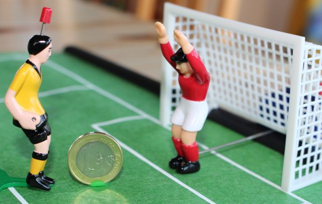 Der Torwart bei einem Tipp-kick-Spiel steht mit erhobenen Händen im Tor, und die Ein-EURO-Münze rollt auf ihn zu.