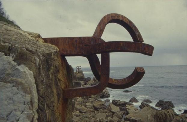 Die Skulptur befindet sich an einer Klippe über dem steinigen Strand, und leichte Wellen rollen auf. Die Skulptur ähnelt einem EURO-Zeichen: einem Halbkreis mit einem Mittelstrich.