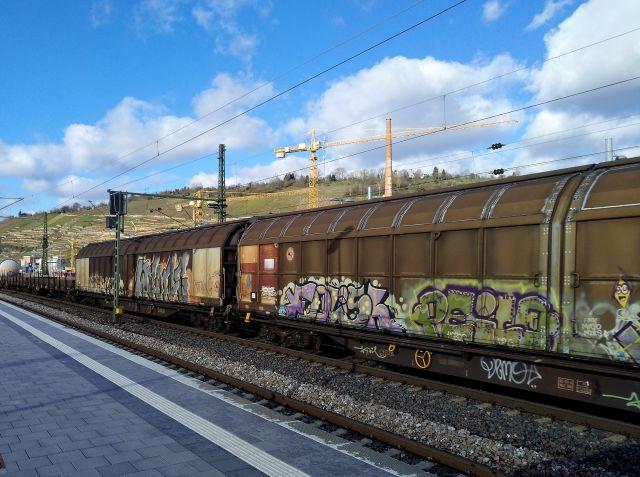 Mit Graffiti versehene Güterwaggons rollen an Esslingen vorbei.