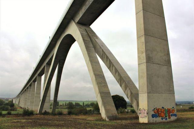 ICE-Brücke aus hellem Beton mit Stützbögen über Wiesen und Feldern.