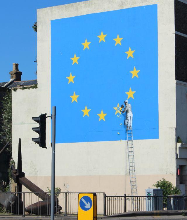 Blaue EU-Flagge mit gelben Sternen an einer Hauswand. Ein ebenfalls gemalter Handwerker ist dabei, einen Stern zu entfernen.
