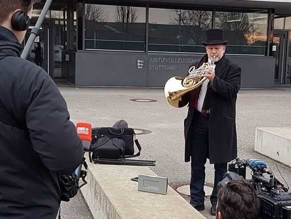 Rudolf Diebetsberger mit dunklem Mantel und Hut spielt Horn vor dem Eingang der JVA in Stuttgart-Stammheim.