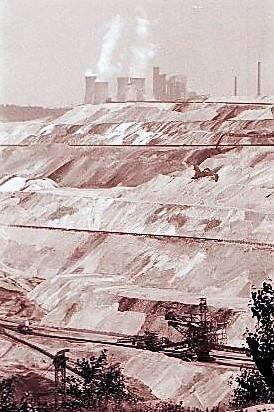 Dampfende Kühltürme eines Kraftwerks, das die im Tagebau gewonnene Braunkohl verstromt.