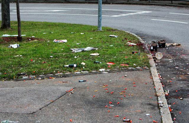 Auf einer kleinen Anlage mit grünem Gras liegen verstreut die Überreste des Feuerwerks.