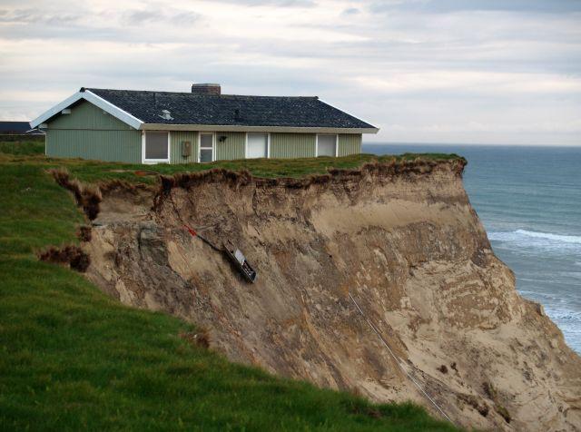 Aufeiner bräunlichen Klippe steht ein Ferienhaus, das demnächst abstürzen wird.