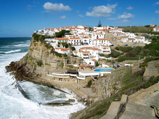 Weiß getünchte Häuser mit roten Dächern in einem malerischen Dorf an der Atlantikküste Portugals. Auf einer Klippe sind sie relativ sicher, aber neue Gebäude liegen auf Meeresniveau.