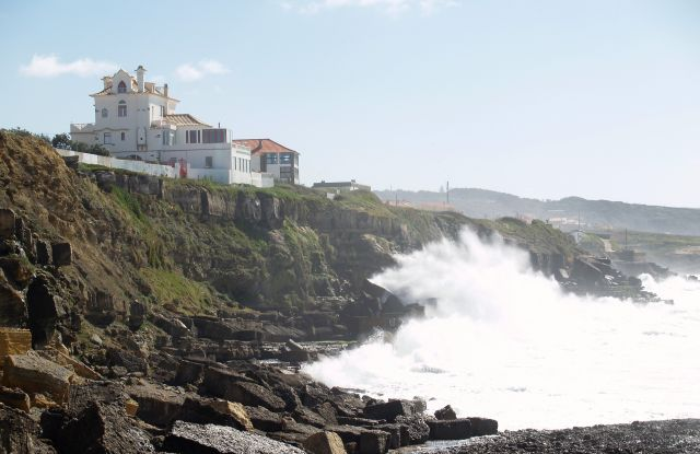 Gebäude auf einer Klippe in Portugal, das fast von den Wellen erreicht wird.