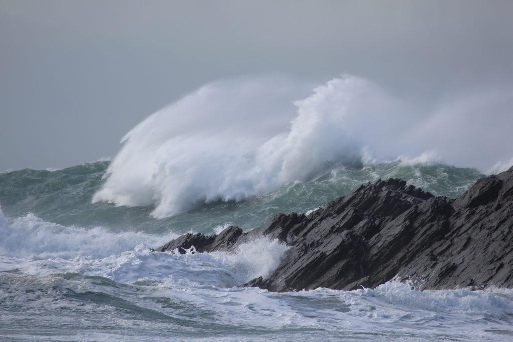 Grünliche Wellen mit weißer Gischt am Clogher Beach. Sie sind die Vorboten des nächsten Sturms.