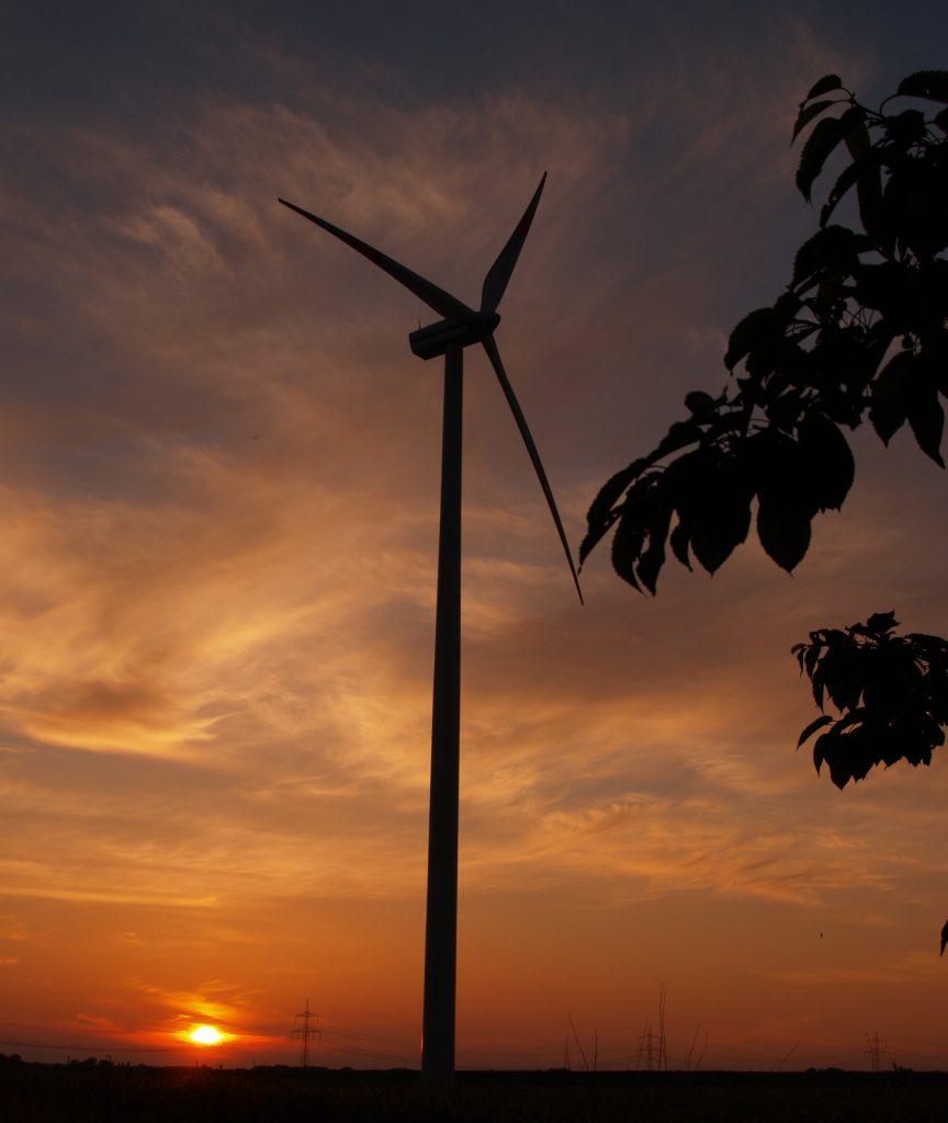 Windkraftanlage vor Abendhimmel.