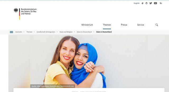 Zwei Frauen, die sich umarmen, eine davon mit Kopftuch.
