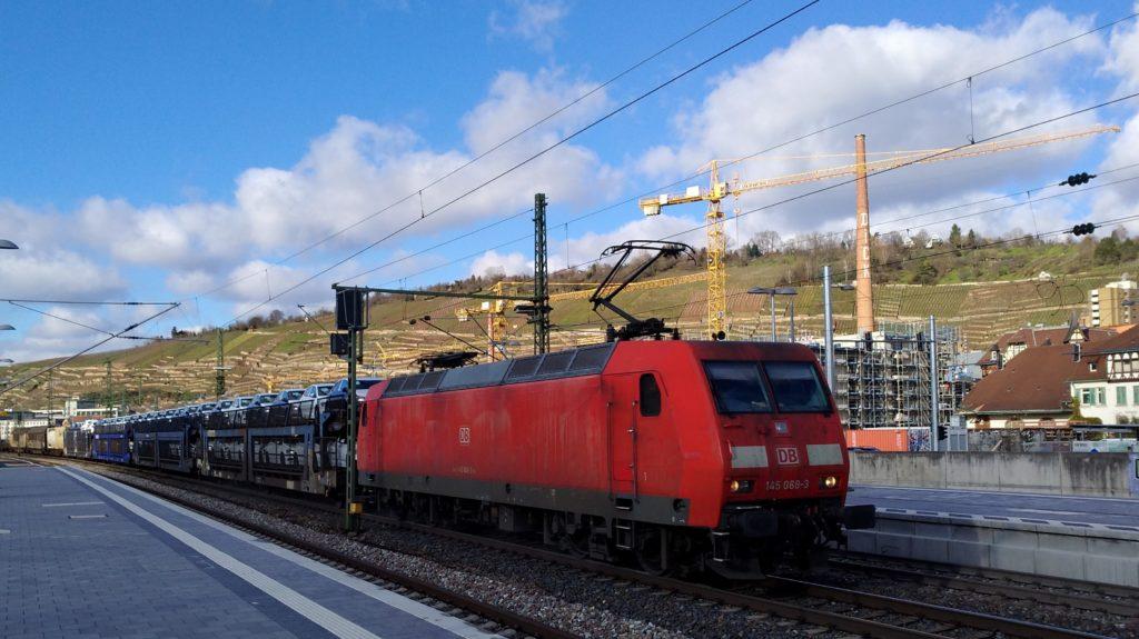Rote Elektrolok zieht einen Güterzug.