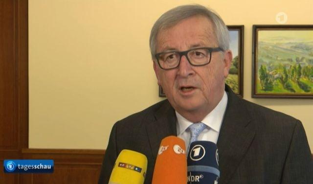 Jean-Claude Juncker im Bild mit verschiedenen Mikrofonen.