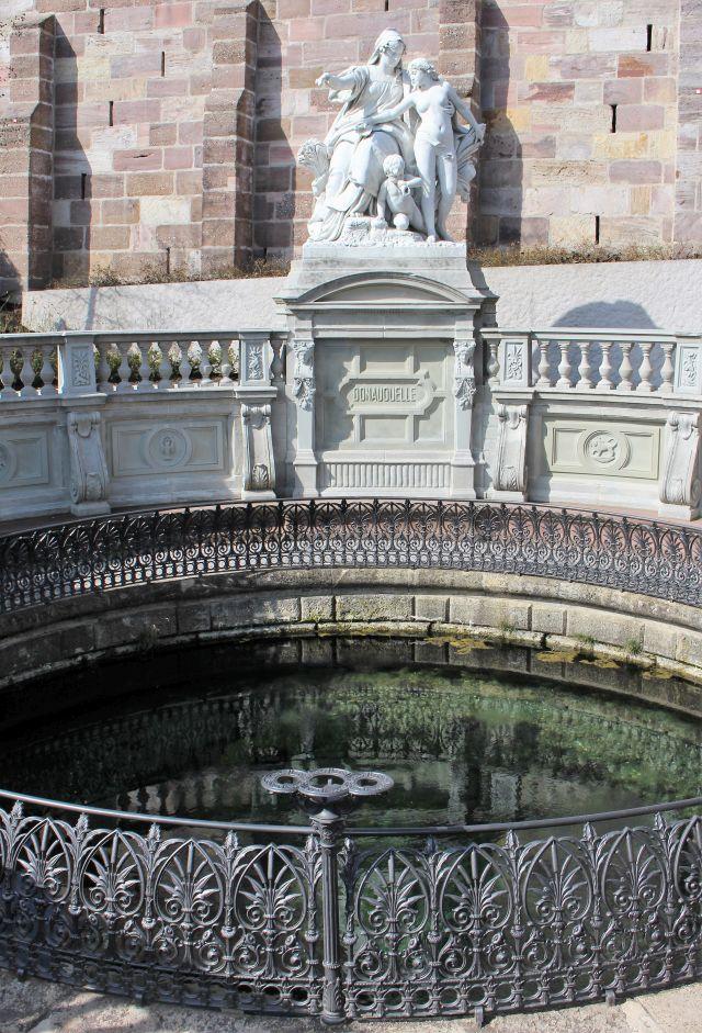 Die weiße Skulptur von Adolf Heer überragt die Donauquelle und stellt die Mutter Baar dar, die ihrer Rochter, der Donau, den Weg zum Schwarzen Meer weist.