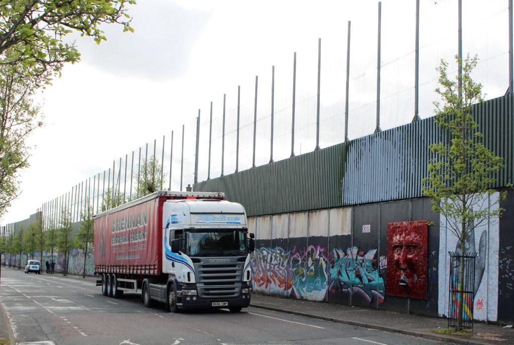 Ein Lkw fährt an der Peace Wall entlang, die mit 8 bis 12 Metern hohen Mauern und Zäunen katholische und protestantische Stadtteile in Belfast trennt.