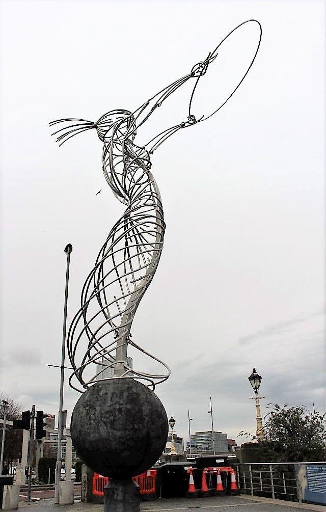 Eine Frauengestalt aus Metall mit einem dünnen Stahlreifen in beiden Händen.