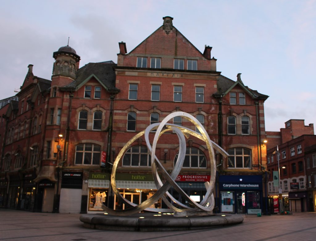 Verschlungene Kreise symbolisieren Textil- und Werftindustrie. Die moderne Installation bildet einen interessanten Gegensatz zum historischen Gebäude im Hintergrund.