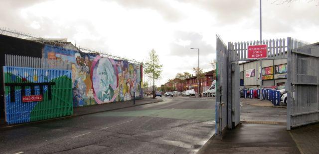 Das Tor zwischen der Falls Road und der Shankill Road wird bei Nacht geschlossen. Im Hintergrund einige politische Murals (Wandbilder).