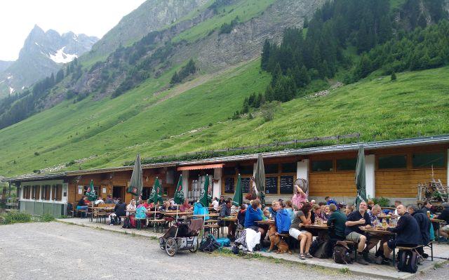 Zahlreiche Gäste essen auf der Sulzl Alm in Tirol vor dem Gebäude.