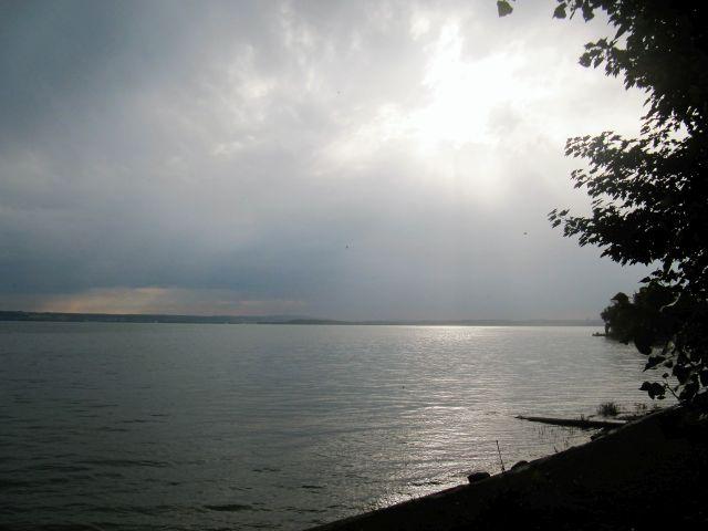 Die Wasseroberfläche des Bodensees mit einer hinter den Wolken verborgenen Sonne.