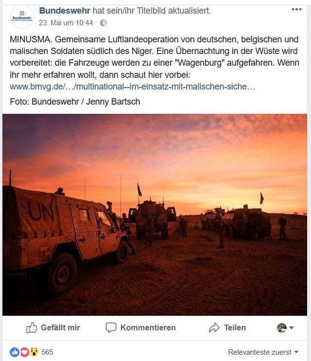 Bundeswehr-Fahrzeuge bilden vor dem rötlichen Nachthimmel eine Wagenburg.