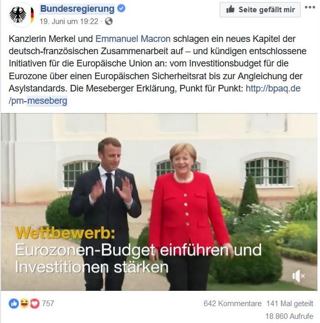 Macron im Anzug gestikulierend neben Merkel im roten Blazer vor Schloss Meseberg.