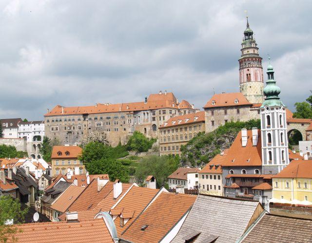 Blick auf das Schloss in Cesky Krumlov: Hellbraune Fassaden mit roten Ziegeldächern.