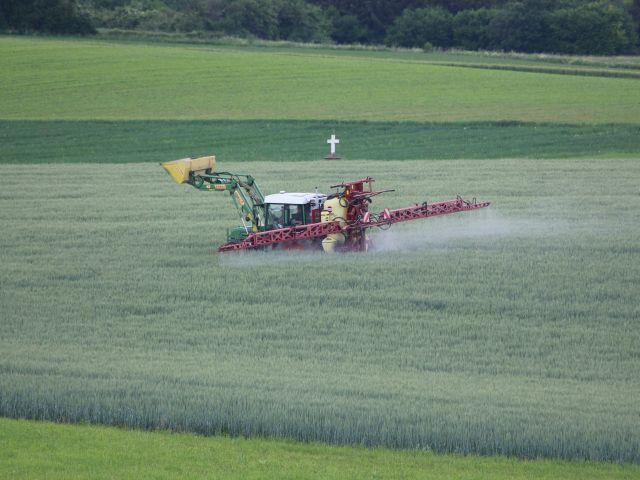 Traktor beim Versprühen chemischer Hilfsmittel. Im Hintergrund ein mahnendes weißes Steinkreuz.