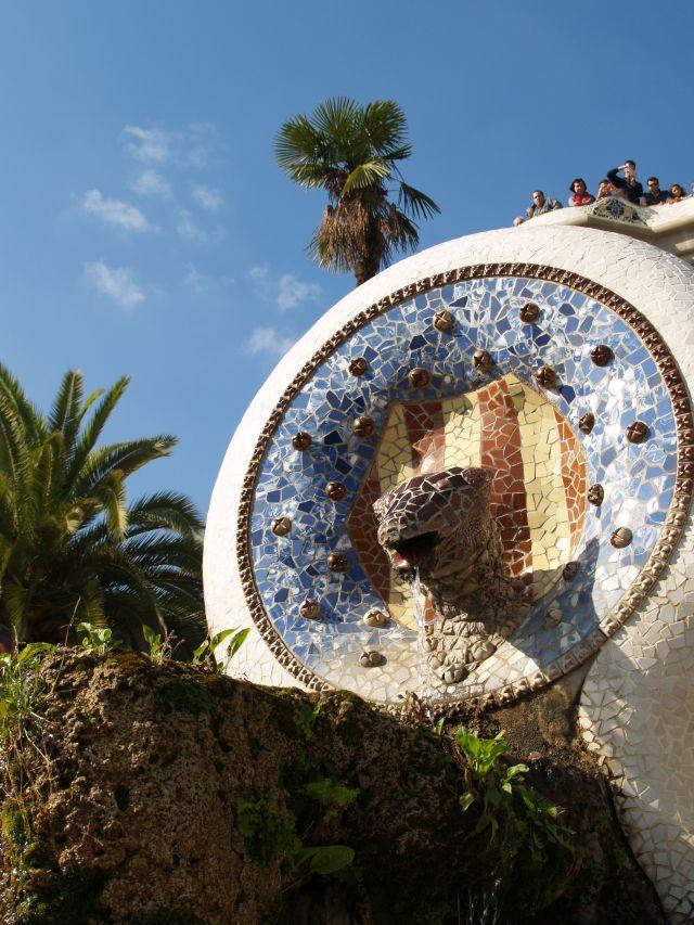 Buntes Mosaik m it vielen Blautönen, umgeben von Palmen.