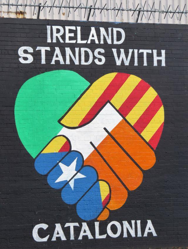 """Mural / Wandbild im nordirischen Belfast mit dem Text """"Ireland stands with Catalonia"""" und Händen, die ineinander greifen in den Nationalfarben."""