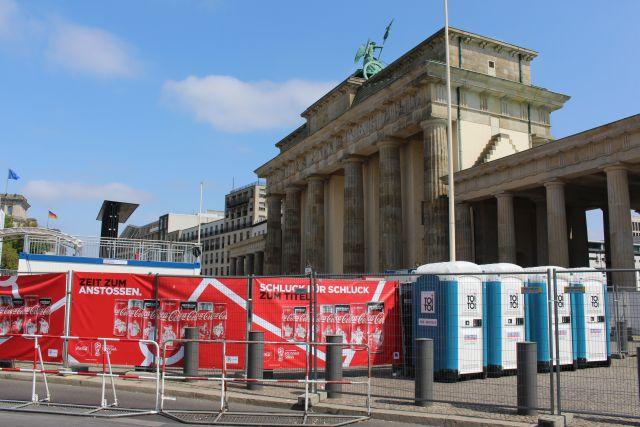 Brandenburger Tor umgeben von Werbung und Klohäuschen.