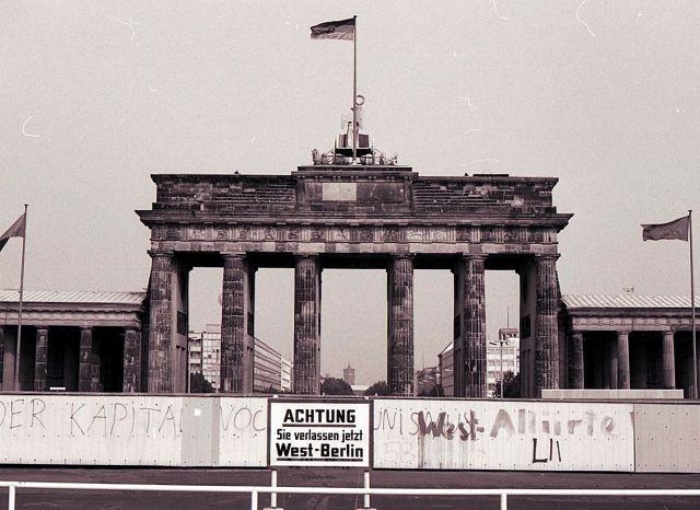 """Hinweisschild """"Achtung. Sie verlassen jetzt West-Berlin"""" vor der Mauer und dahinter das Brandenburger Tor."""