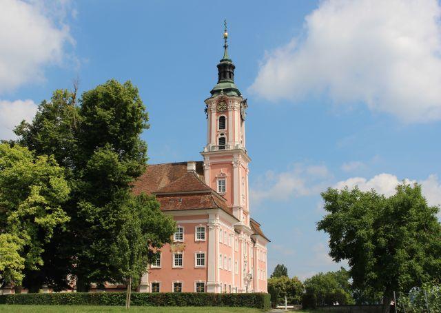 Die barocke Basilika Birnau ist in einem rötlichen Grundton gehalten und umgeben von Bäumen.