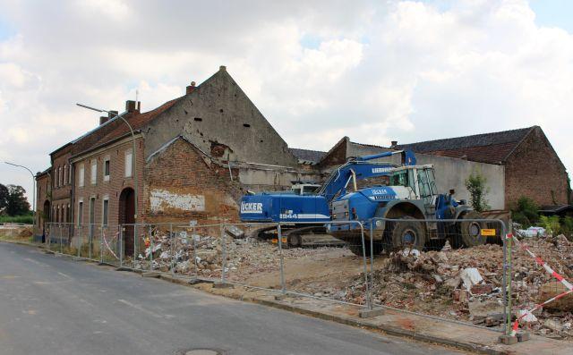 Bagger vor einem Abrissgebäude.