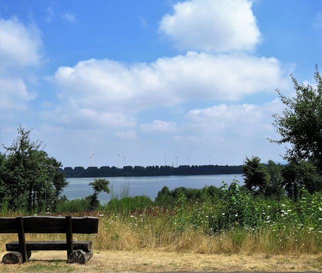 Eine Bank läd vor dem Blaustein-See, der balu schimmert, zum Verweilen ein.