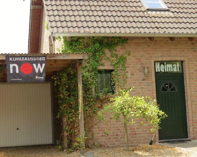 """An einer grüne Haustür prangt der Schriftzug """"Heimat"""" und daneben """"Kohleausstieg NOW""""."""