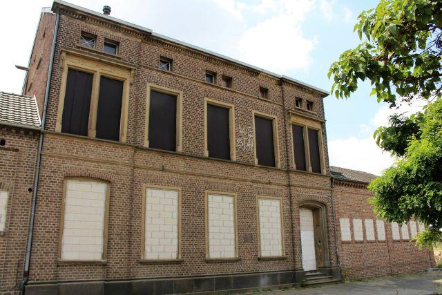 Alle Fenster an diesem zweistockigen Gebäude sind bereits zugemauert.